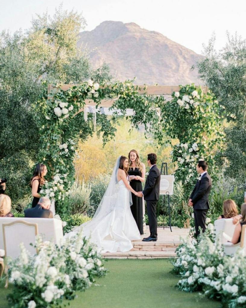 In questa foto un amica degli sposi celebra il loro matrimonio civile su un prato circondati da fiori e piante. Il rito si svolge sotto ad un gazebo di legno con piante rampicanti. Gli sposi si tengono per mano durante la celebrazione