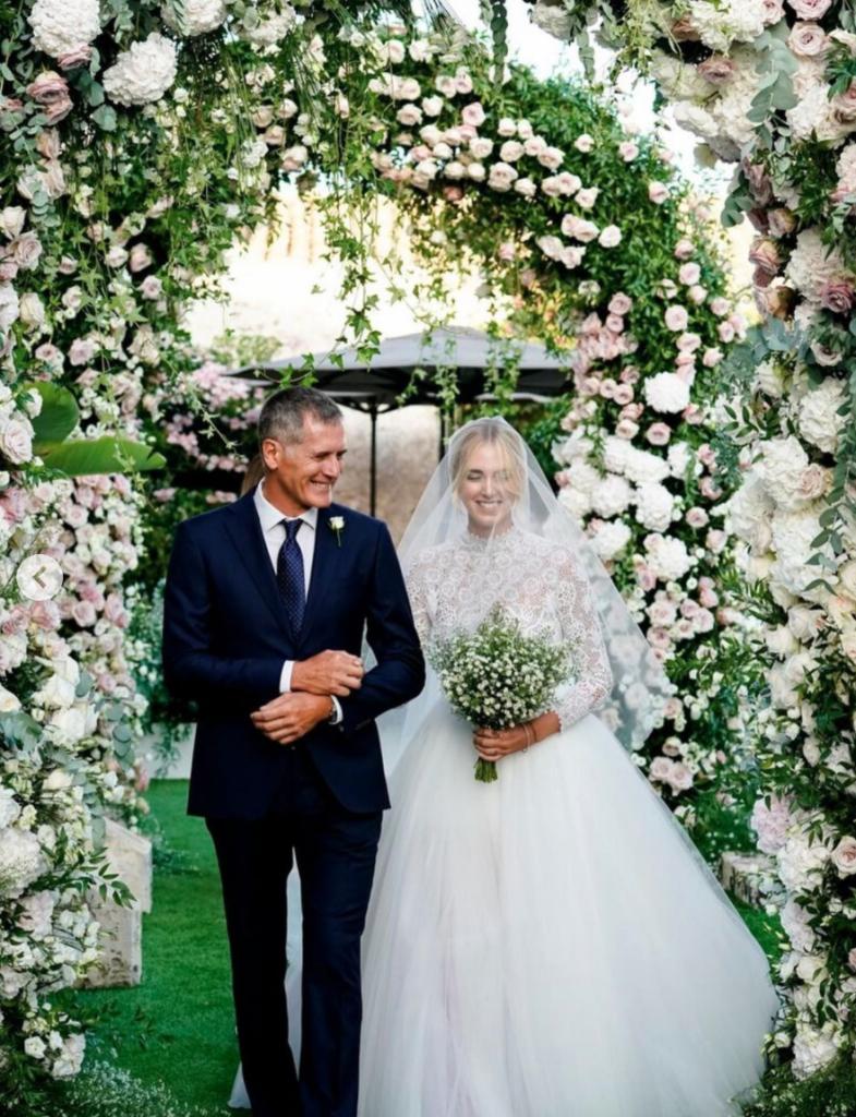 In questa foto Chiara Ferragni e il papà sorridenti fanno il loro ingresso nel giorno delle nozze. Sono circondati di fiori rosa e bianchi. Chiara Ferragni ha un bouquet di fiori velo di sposa