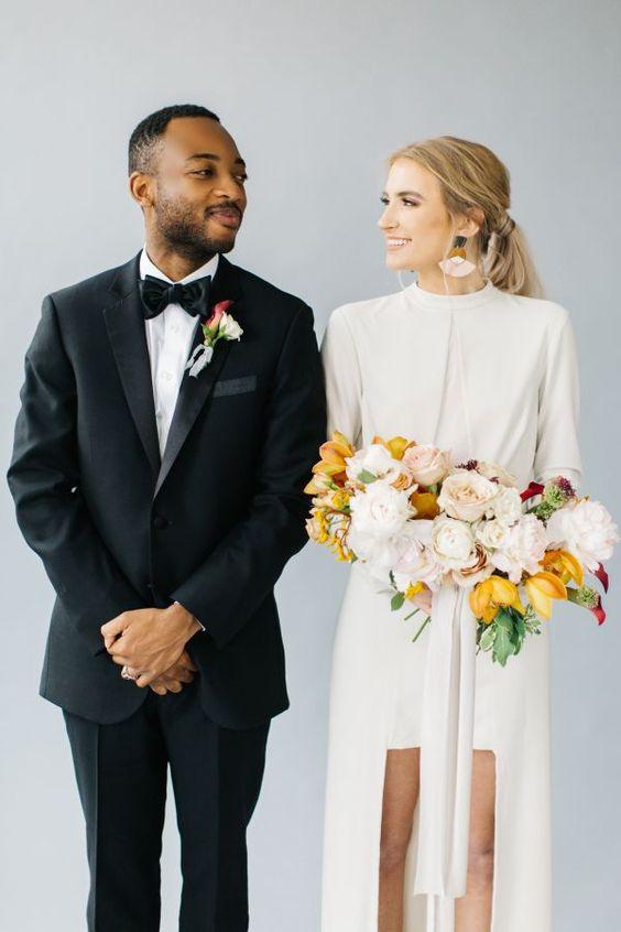 In questa foto due sposi si guardano sorridenti. Lei tiene un bouquet di fiori gialli e bianchi e indossa una tuta con shorts e giacca