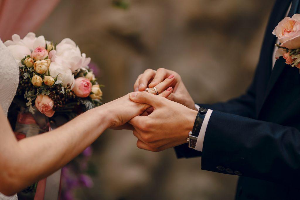 In questa foto vengono riprese solo mani degli sposi. Lo sposo mette la fede al dito della sposa. Si intravede anche il bouquet