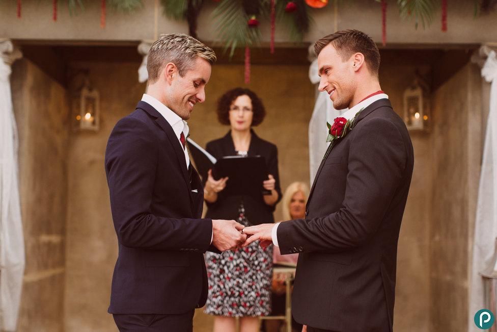 In questa foto due sposi gay si scambiano le fedi davanti all'officiante del rito civile