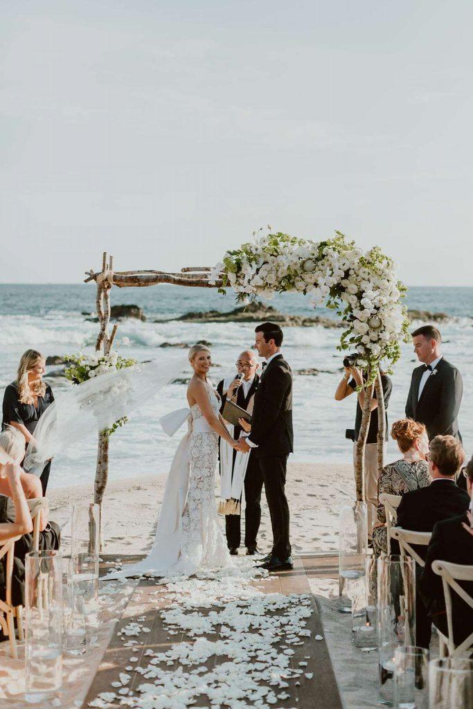 In questa foto una sposa sorridente si volta verso gli invitati durante la cerimonia del suo matrimonio civile in spiaggia