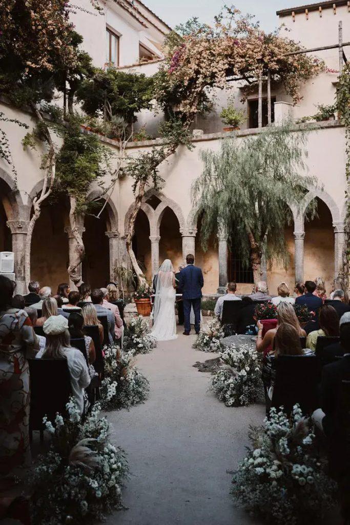 In questa foto un matrimonio civile nella corte interna di un castello circondata da fiori rampicanti. Lungo il corridoio della location sono stati sistemati a terra dei cesti di fiori bianchi e rosa