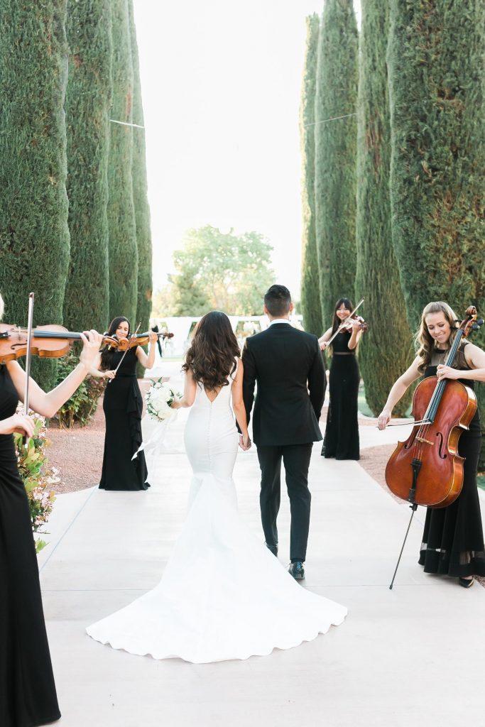 In questa foto due sposi fanno il loro ingresso in un giardino accolti da un quartetto d'archi