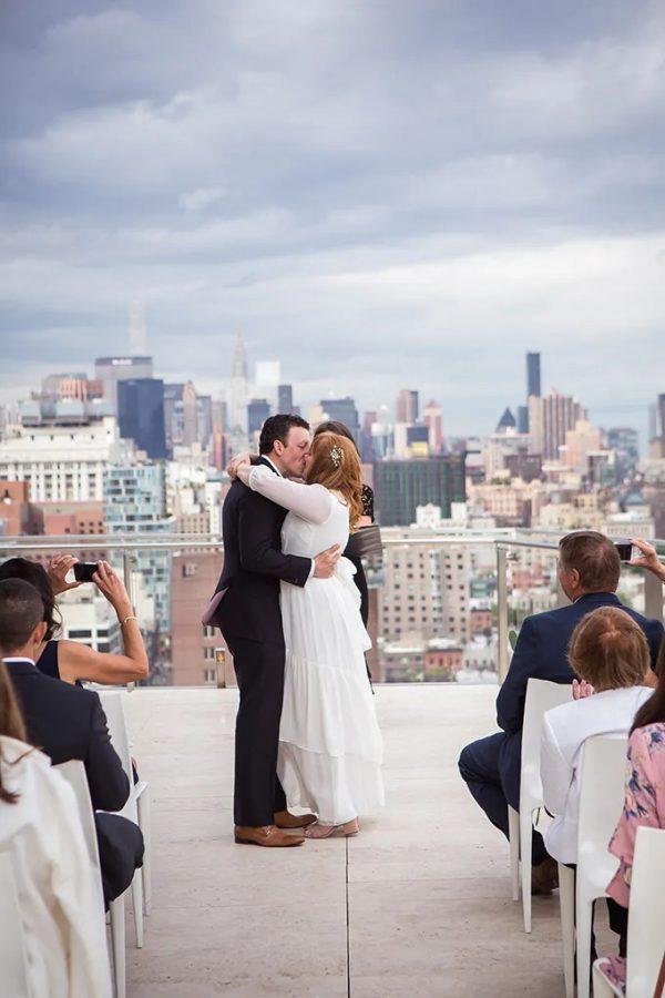 In questa foto due sposi si baciano alla fine del loro matrimonio civile sui tetti di New York. Sullo sfondo si intravede la città