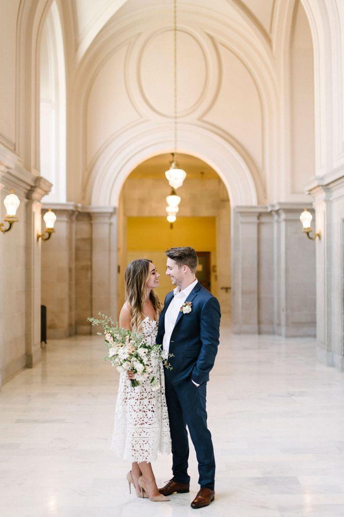 In questa foto due sposi si guardano sorridenti nel corridoio di marmo del Comune dove celebreranno il matrimonio. La sposa tiene nella mano destra un bouquet a braccio di fiori bianchi e rosa cipria. Lo sposo indossa un abito blu senza cravatta ma con bottoniera