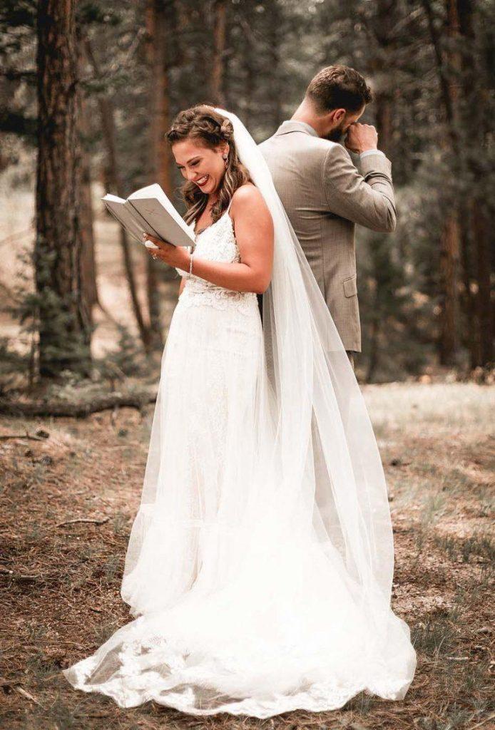 In questa foto una sposa ride mentre legge le sue promesse allo sposo che, in piedi e di spalle, si asciuga le lacrime