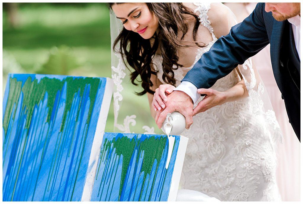 In questa foto due sposi celebrano il rito simbolico dei colori facendo scivolare su una tela vernice azzurra, verde e bianca