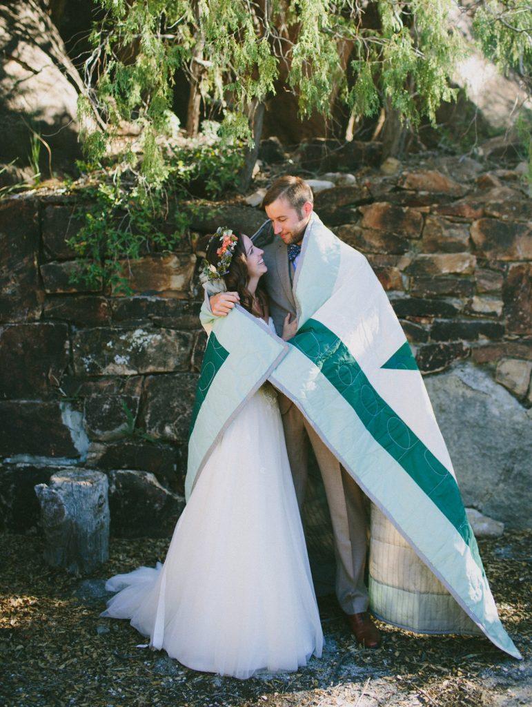 In questa foto due sposi si avvolgono con una coperta bianca e verde dopo il rito della chuppah