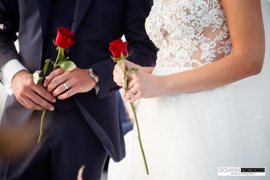 In questa foto sono riprese le mani dei due sposi mentre tengono una rosa rossa ciascuno per il rito simbolico della rosa