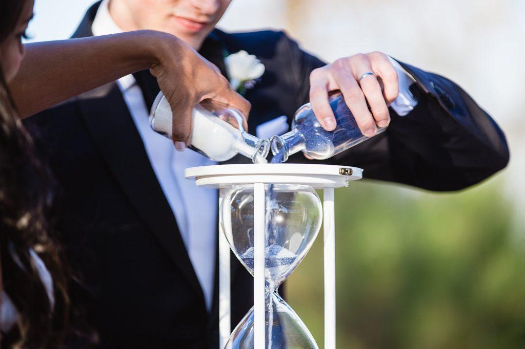 In questa foto due sposi versono sabbia bianca e blu in una clessidra durante il rito simbolico della sabbia