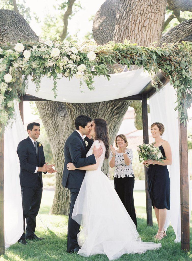 In questa foto due sposi si baciano sotto il baldacchino del loro matrimonio civile mentre testimoni e celebranti applaudono