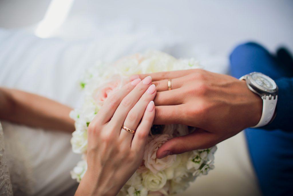 In questa foto le mani di due sposi una sopra all'altra poggiate su un bouquet di rose bianche mostrano le loro fedi