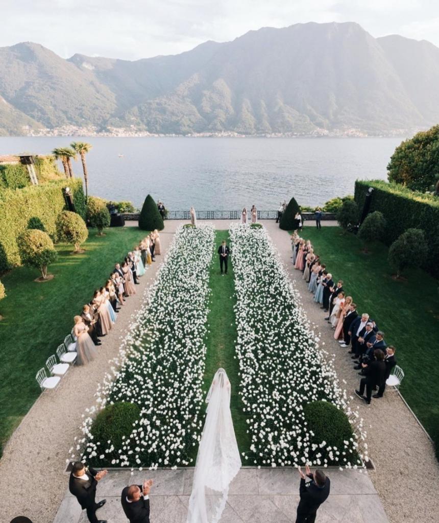 In questa foto l'ingresso della sposa nella location del suo matrimonio civile sul lago di Como lungo un corridoio di fiori bianchi disposti su un prato. Ai lati sono presenti gli invitati