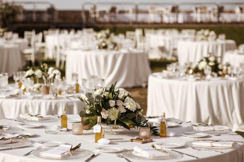 In questa foto tavoli matrimonio decorati con centrotavola di fiori bianchi e bottigliette d'olio