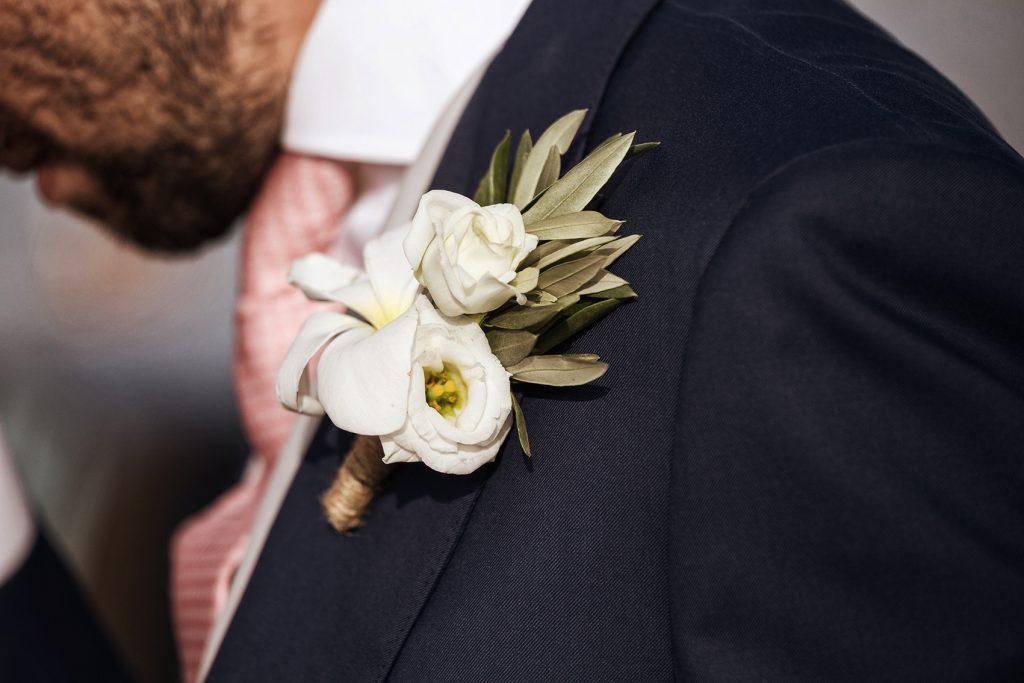 In questa foto una bottoniera di rose bianche, pomelie e rametti d'ulivo