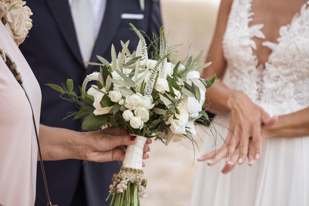 In questa foto un bouquet da sposa con rose bianche, foglie d'ulivo e rametti di Veronica. Il bouquet è decorato con un nastro di passamaneria