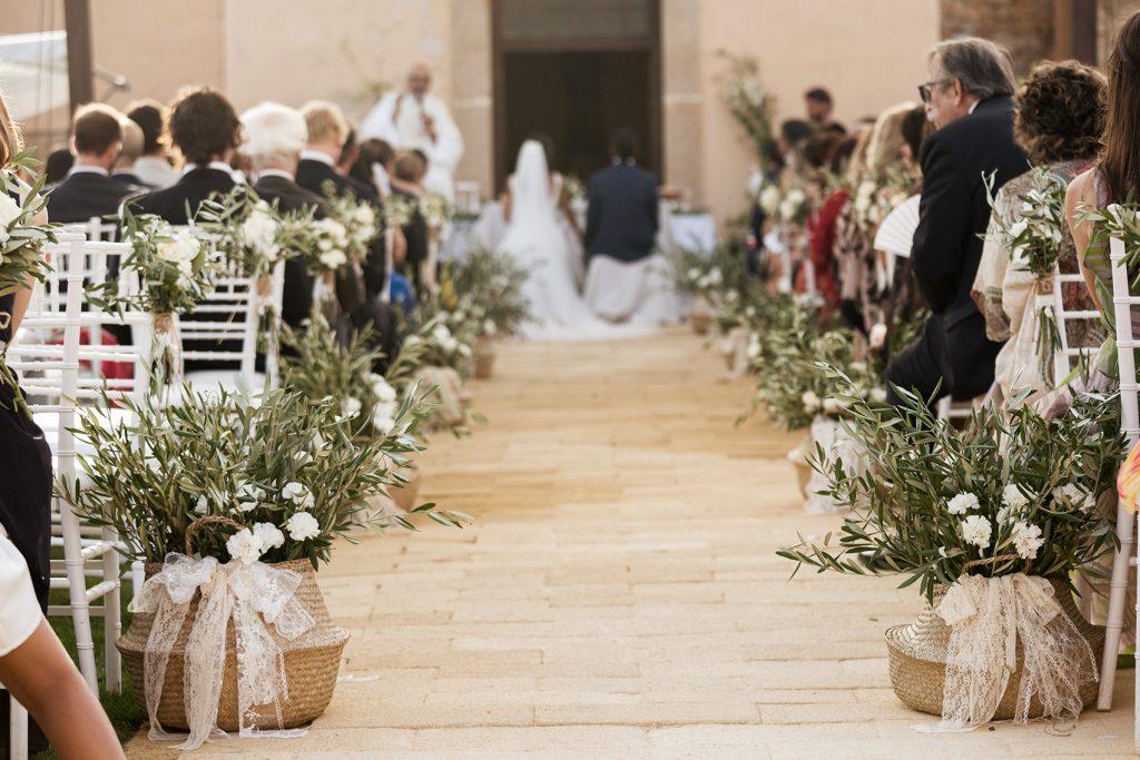 In questa foto un matrimonio religioso all'aperto. In primo piano sono riprese ceste di paglia con ramoscelli d'ulivo. Sullo sfondo si intravedono gli sposi seduti al tavolo nozze