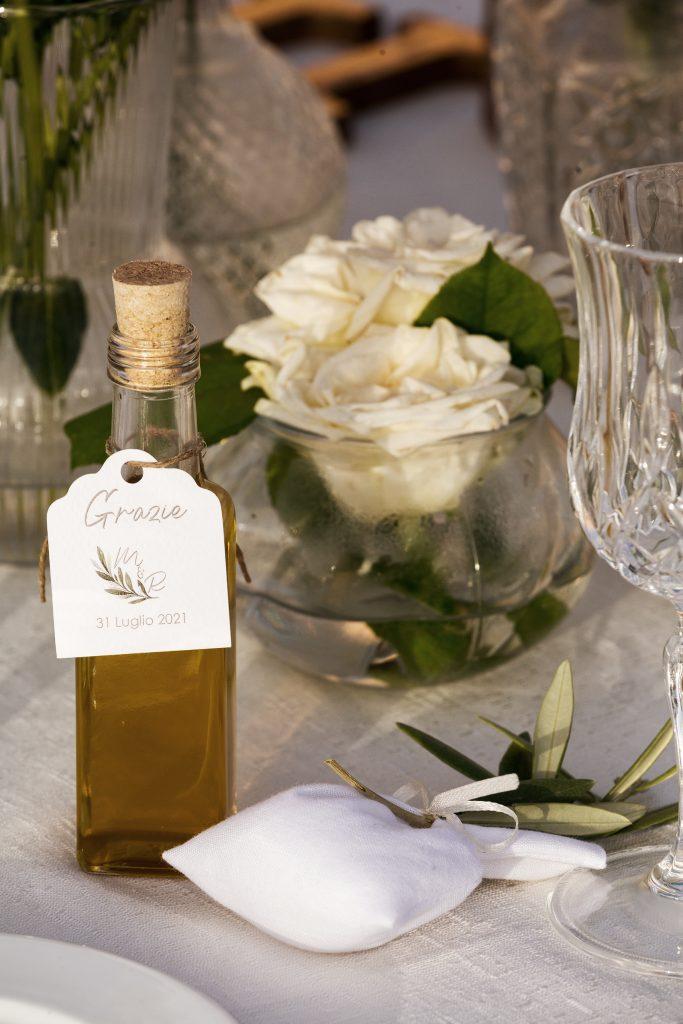 In questa foto una bomboniera gourmet composta da una bottiglietta di olio d'oliva decorata con un cartoncino di ringraziamento con un ramoscello d'ulivo. Accanto un sacchetto per confetti bianco. Sono poggiati su un tavolo e sullo sfondo si intravede un centrotavola realizzato con un vaso tondo d'acqua e rose bianche