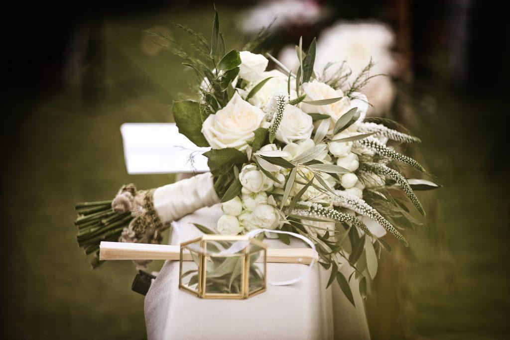 In questa foto il dettaglio del banco degli sposi su cui è poggiato il bouquet della sposa con rose bianche, foglie d'ulivo e passamanerie sul gambo. In primo piano vengono mostrati il ventaglio e la scatolina portafedi colore oro a forma esagonale
