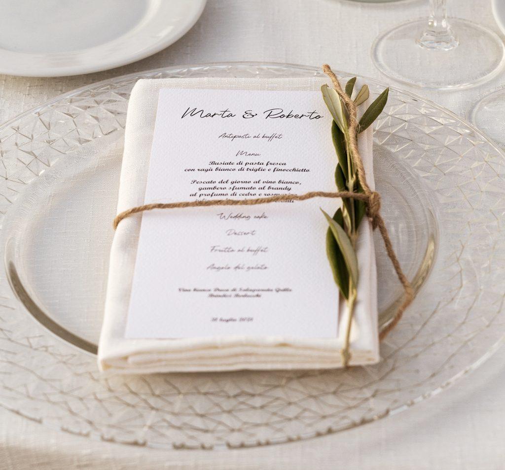 In questa foto il dettaglio di una mise en place di matrimonio in stile minimal chic con un sottopiatto di vetro trasparente su cui è poggiato un tovagliolo con menù personalizzato fermati da un filo di spago con un ramoscello d'ulivo