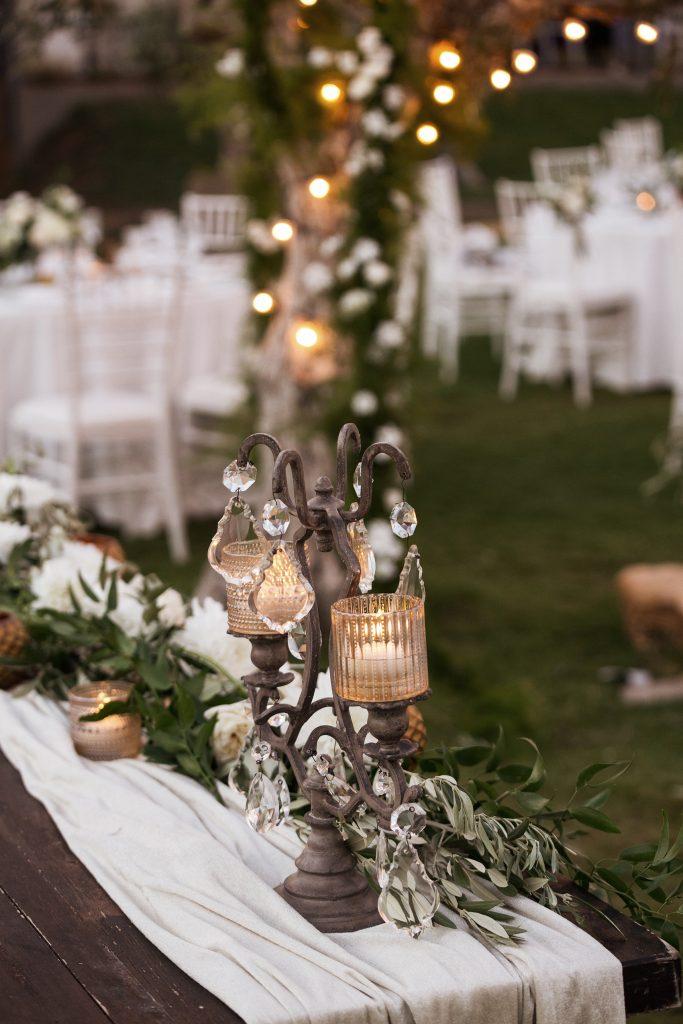 In questa foto il dettaglio della decorazione del tavolo degli sposi con un candelabro in ottone, cristalli pendenti e, attorno, rametti d'ulivo su un drappo di velluto
