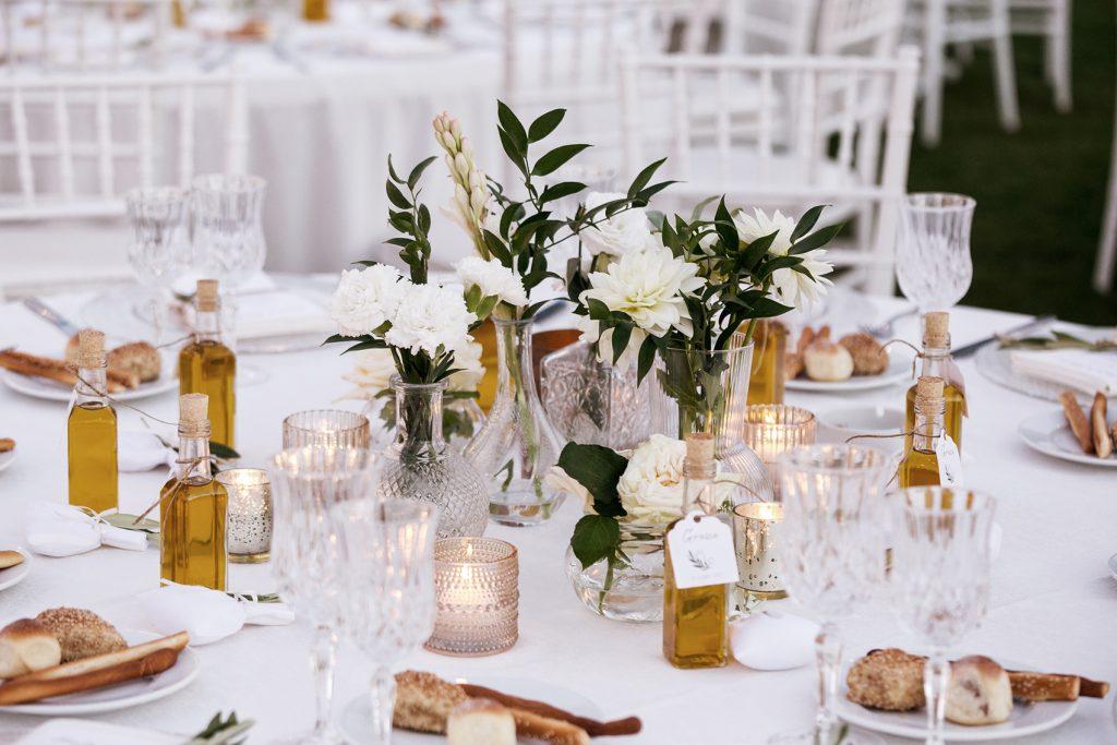 In questa foto un tavolo di nozze con tovagliato bianco, bicchieri e piatti di vetro trasparente, bottigliette di olio e centro tavola di fiori bianchi e foglie d'ulivo
