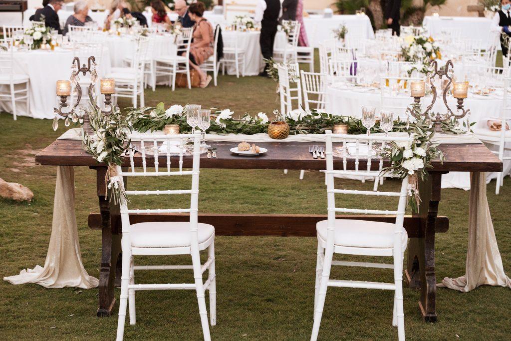 In questa foto il tavolo degli sposi ripreso di spalle con due chiavarine bianche decorate con rametti di fiori bianchi e rametti d'ulivo. Il tavolo nudo rettangolare è decorato con un drappo di stoffa avorio e un runner di foglie d'ulivo. Sul tavolo sono presenti anche due candelabri d'ottone e  portacandele colore oro