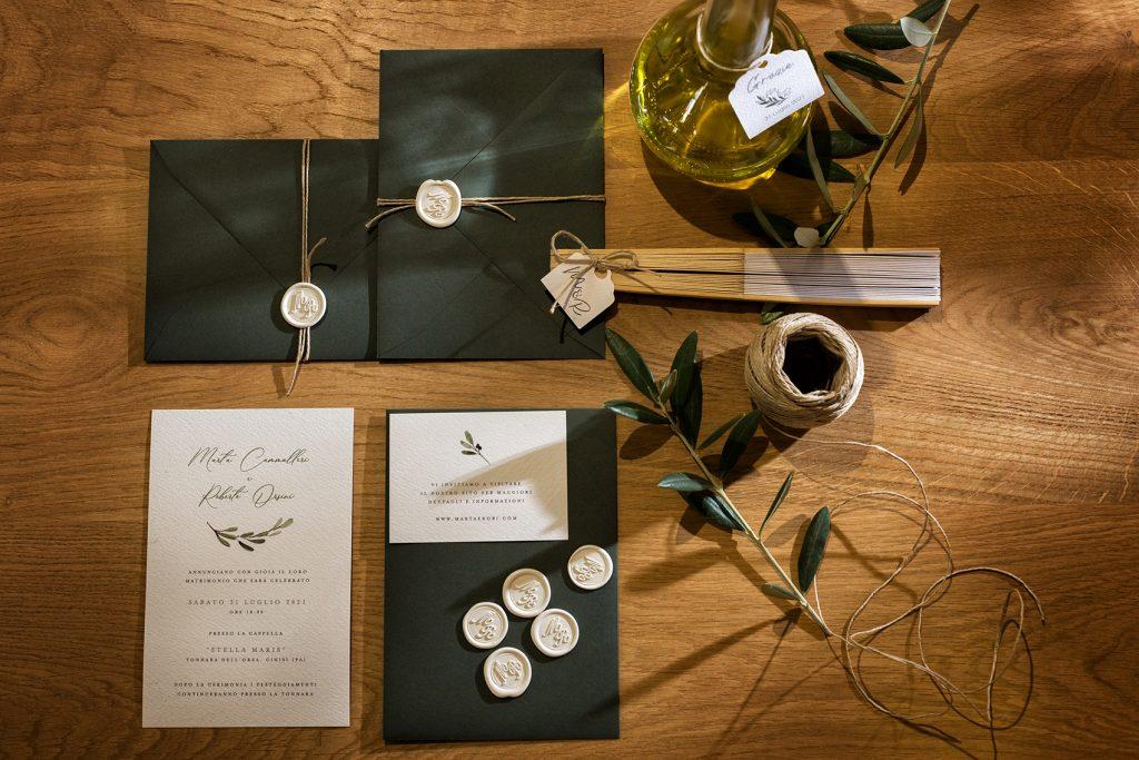 in questa foto una partecipazione di nozze a parte composta da una busta verde oliva e invito bianco con decorazioni di foglie d'ulivo. Un ramoscello è poggiato sul tavolo insieme ad un ventaglio, ad un rotolo di spago e ad una bottiglietta di olio