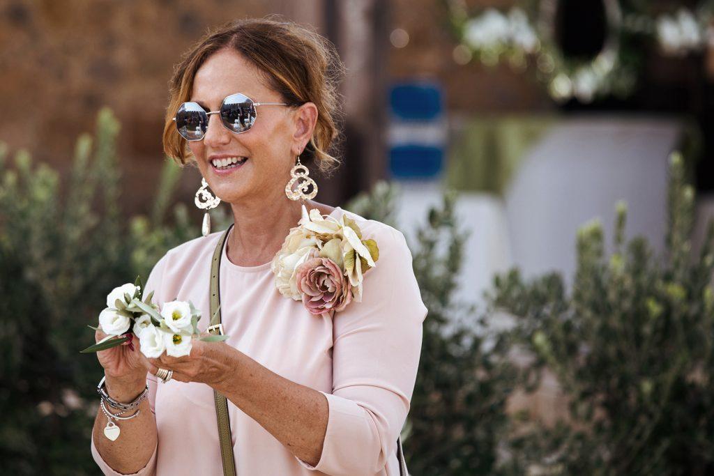 In questa foto la wedding planner Antonella Candido mentre sorride tenendo tra le mani dei fiorellini bianchi