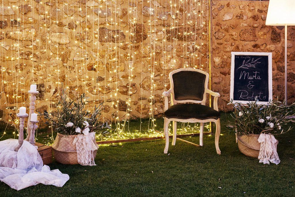 In questa foto un angolo photo booth di un matrimonio realizzato con una tendina di piccole luci, un poltrona di velluto, un cesto di paglia con ramoscelli d'ulivo e candelabri in ottone