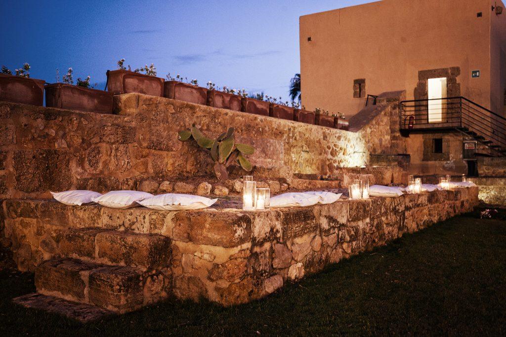In questa foto un salottino di un ricevimento di nozze realizzato su un muretto di pietra viva con cuscini bianchi e portacandele trasparenti
