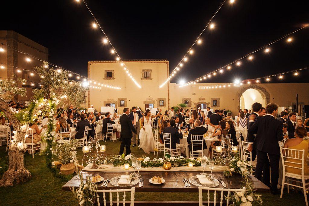 In questa foto un ricevimento di nozze su un prato in un casale con tetto di luci. Tra gli invitati, al centro, si intravedono gli sposi