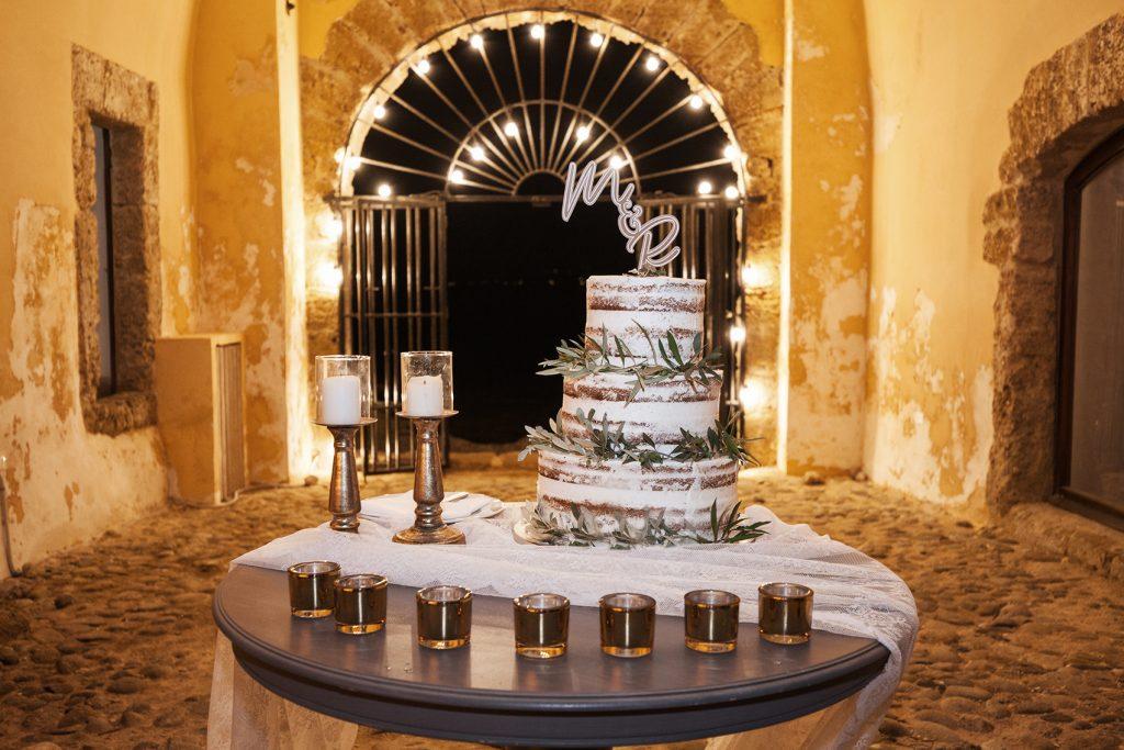In questa foto una torta nuziale del tipo naked cake con foglie d'ulivo sui piani, poggiata su un tavolo decorato con un drappo di stoffa bianca, piccoli portacandele colore oro, due candelabri