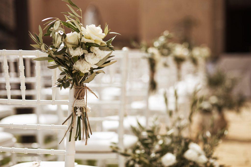 in questa foto il dettaglio dell'allestimento di un matrimonio all'aperto. In primo piano è ripreso in mazzetto di rose bianche e foglie d'ulivo attaccato ad una sedia chiavarina
