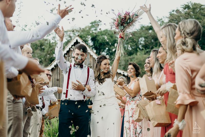 In questa foto due sposi felici attraversano il corridoio della location del matrimonio civili mentre gli invitati lanciano petali e foglie