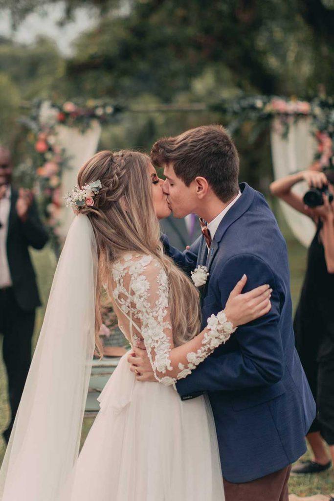 In questa foto due sposi si baciano alla fine della cerimonia del loro matrimonio civile. La sposa indossa un abito con maniche con ricami floreali e al velo ha attaccato dei piccoli fiori rosa