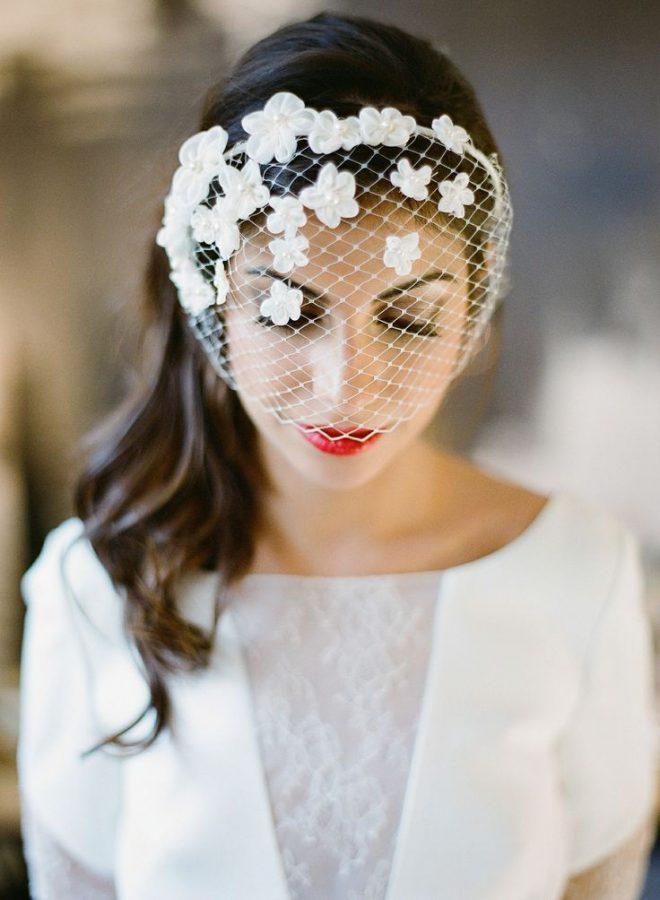 In questa foto una modella indossa una veletta da sposa con fiori 3D e perline perfetta per un matrimonio civile. Tiene il viso leggermente abbassato in avanti con gli occhi chiusi e si intravede il rossetto rosso