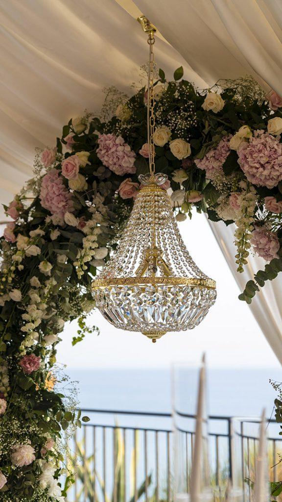 In questa immagine un lampadario di cristallo con sfondo sul mare siciliano
