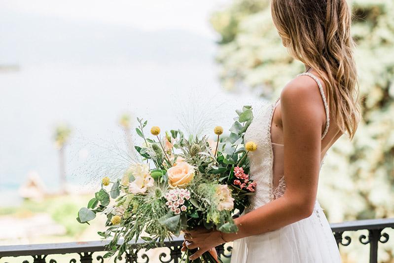 In questa foto una sposa di spalle con un bouquet in mano