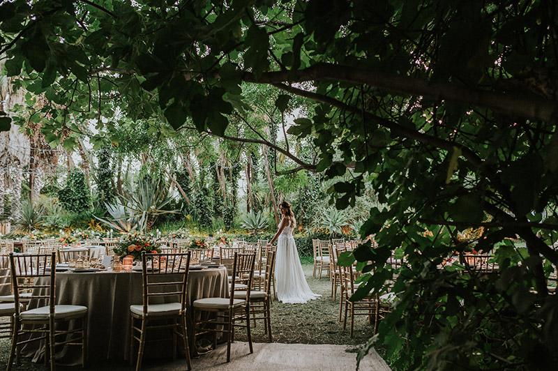In questa foto la sposa posa tra i tavoli del ricevimento di nozze