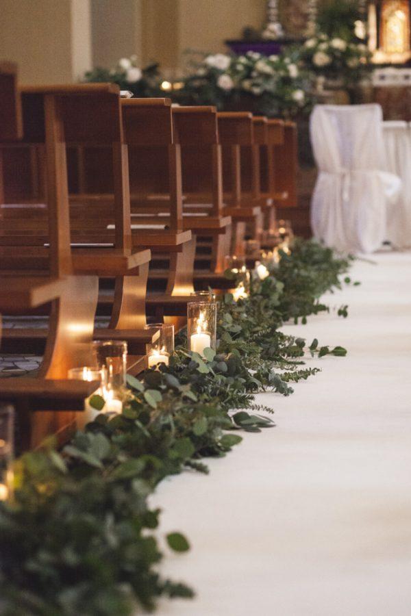 In questa foto una chiesa decorata con un tappeto bianco che ricopre la navata sui cui bordi sono sparse foglie di eucalipto. Sulle foglie sono poggiate candele accese dentro cilindri trasparenti. Sull'altare sono presenti composizioni di foglie e fiori bianchi. All'altare si intravedono sedie bianche