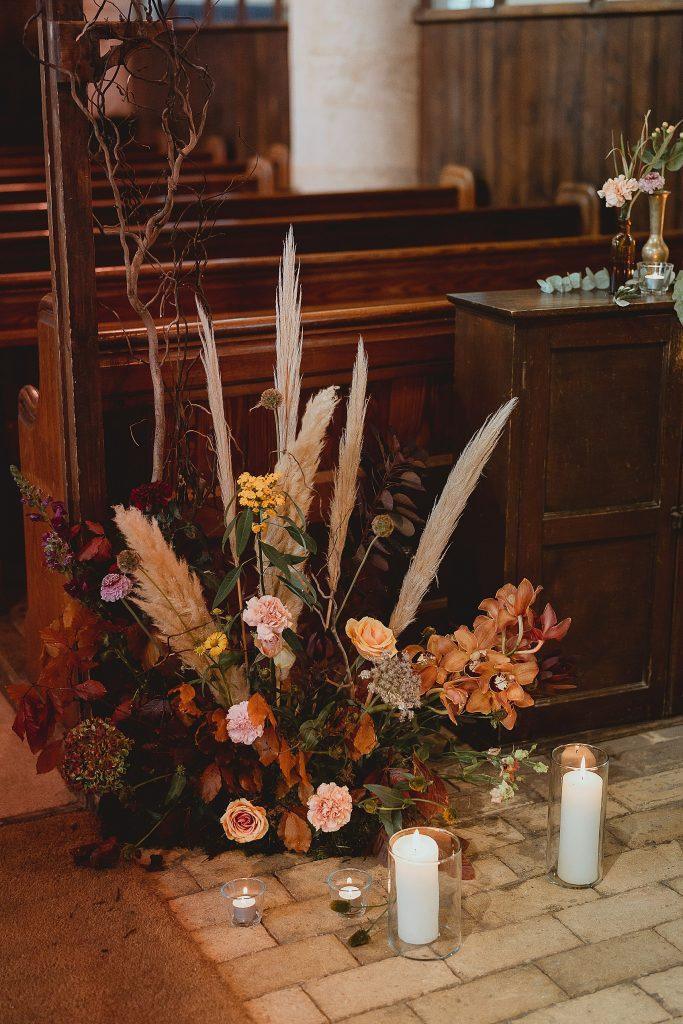 In questa foto una composizione floreale poggiata sul pavimento della chiesa in autunno realizzata con rose gialle, garofani rosa, orchidee arancioni, pampas, foglie e fiori bordeaux