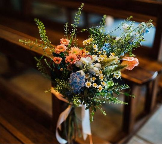 In questa il dettaglio di una decorazione per una chiesa matrimonio realizzata con fiori di campo nei colori del rosa, azzurro e bianco con piccole margherite e foglie di felce