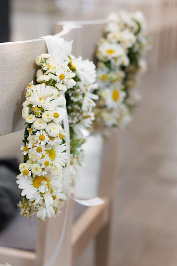 In questa foto due composizioni di margherite piccole e grandi a forma circolare appese con un nastro di raso bianco a due sedie bianche per un matrimonio