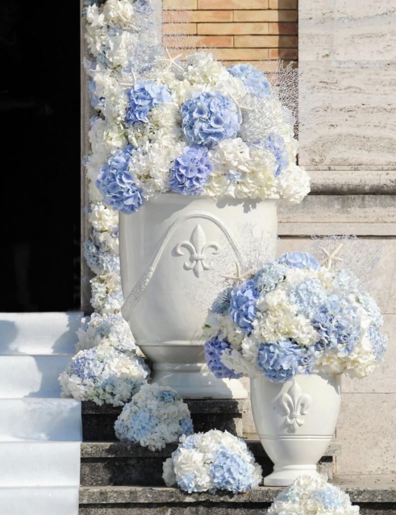 In questa foto addobbi per l'esterno di una chiesa per matrimonio realizzati con ortensie azzurre e bianche. Sui gradini dono sistemati due vasi con all'interno le composizioni di ortensie: il vaso in primo piano è più piccolo di quello più grande in secondo piano. Sui gradini accanto ai vasi sono poggiate piccole composizioni semisferiche di ortensie abbinate. Le ortensie circondano anche l'ingresso della chiesa. Sui gradini di marmo grigio si intravede disteso anche un tappeto bianco