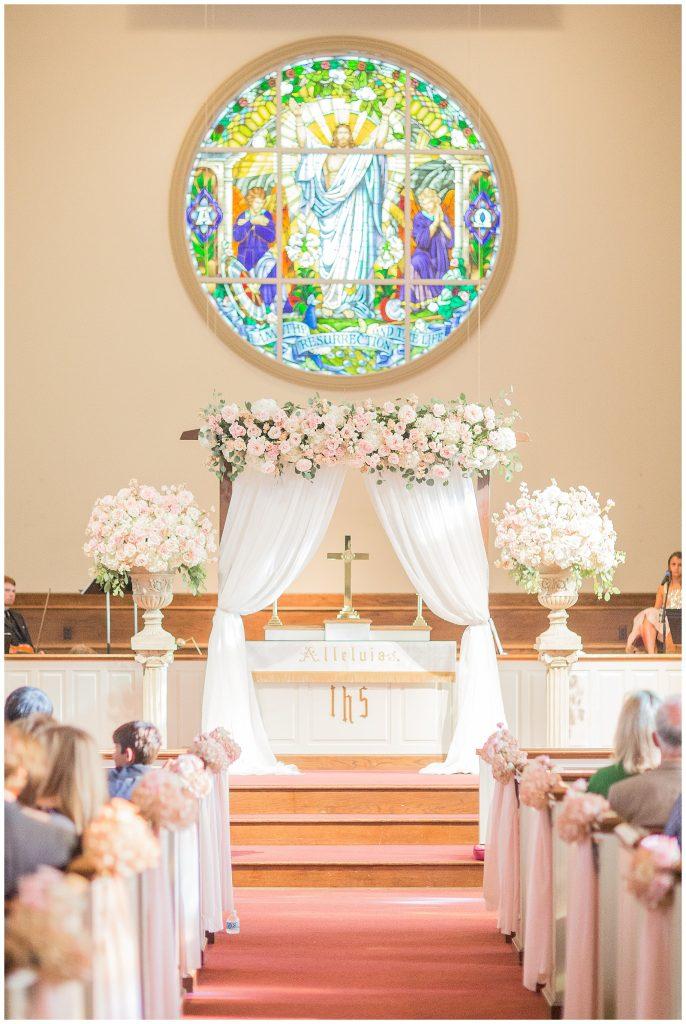 In questa foto una chiesa per matrimonio decorata con rose rosa e bianche lungo la navata e all'altare. Ai banchi della chiesa sono legati piccoli mazzi di fiori da cui pendono nastri rosa cipria. All'altare è montato un arco di legno con due drappi di stoffa bianca. La trave orizzontale è ricoperta di fiori. Ai lati dell'arco sono presenti due grandi vai bianchi poggiati du colonne con composizioni di fiori. Dietro l'arco, al centro è posizionato un crocifisso. Sull'altare è presente una vetrata colorata rotonda  che raffigura il Cristo pantocreatore