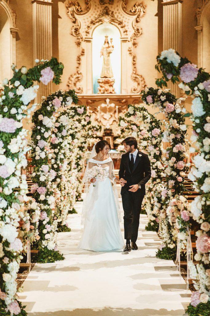 In questa foto una coppia di sposi mentre esce dalla chiesa per matrimonio. La navata centrale è decorata con semiarchi di ortensie bianche e rosa ed eucalipto ed edera rampicanti