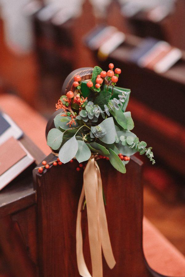 In questa foto il dettaglio della decorazione di una chiesa in inverno. È una piccola composizione di eucalipto e agrifoglio legato con un nastro colore avorio ad uno dei banchi della chiesa