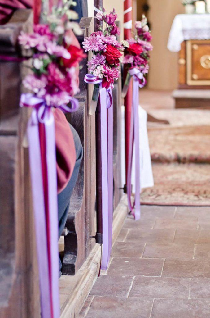 In questa foto 3 decorazioni floreali legate ai banchi di una chiesa. Le decorazioni sono realizzate margherite e fiori di campo colore lilla, rosa e magenta legate da 3 nastri abbinati e pendenti lungo il lato verticale dei banchi della chiesa. A destra si intravede l'altare e un tappeto